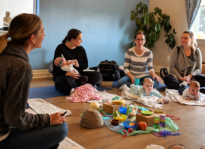 Moms and babies enjoy playing and bonding during a fun class together