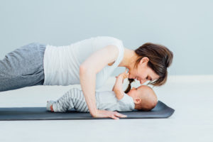 Young mother does physical yoga exercise with her baby boy