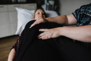 Chiropractor places her hands on pregnant woman's belly during prenatal treatment