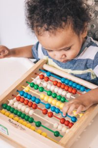 Child working on fine motor control while playing with colorful abacus