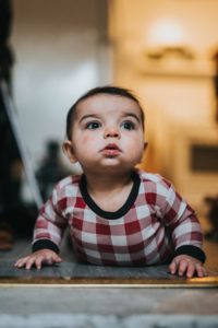 Infant looking up from floor