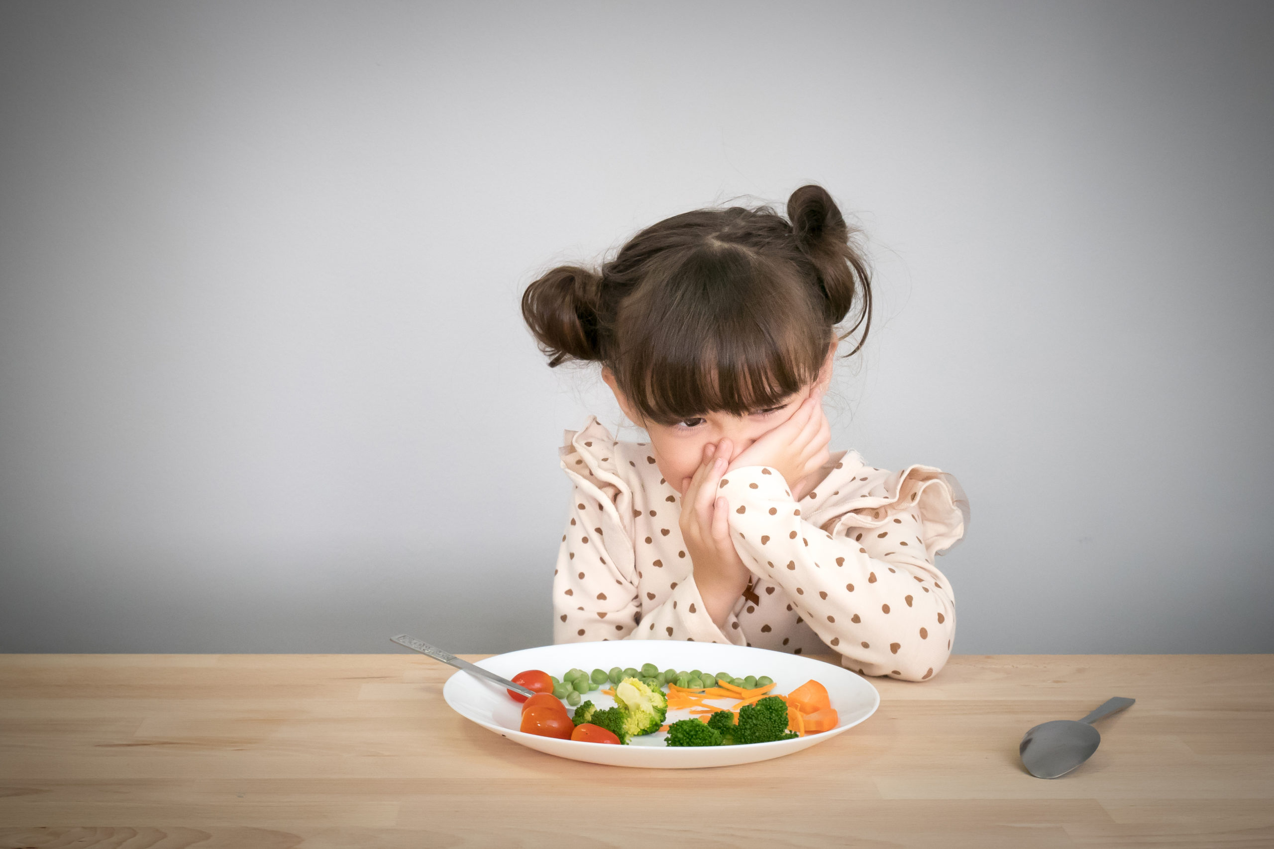 Child plugging her nose in front of plate of vegetables
