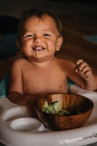 Young child eating solids in a high chair